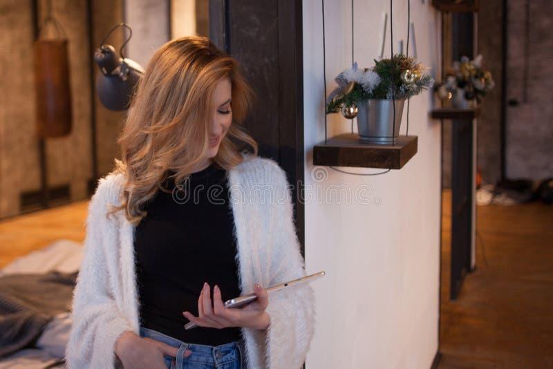 Portrait d'une belle femme dans l'intérieur, les utilisations un smartphone ou le comprimé d'accéder à l'Internet photographie stock libre de droits