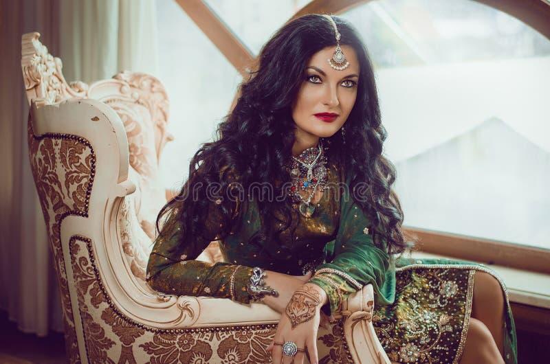 Portrait d'une belle femme dans la robe indienne de chinois traditionnel, avec ses mains peintes avec le mehendi de henné photographie stock