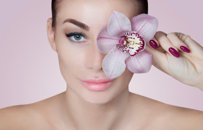 Portrait d'une belle femme dans un salon de station thermale avec une orchidée dans sa main image libre de droits