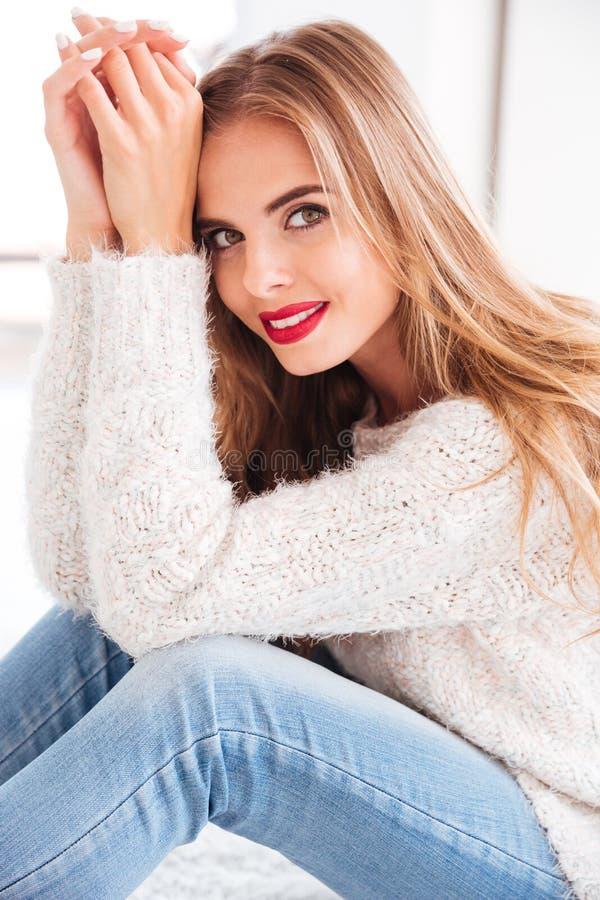 Portrait d'une belle femme de sourire avec la séance rouge de rouge à lèvres photographie stock