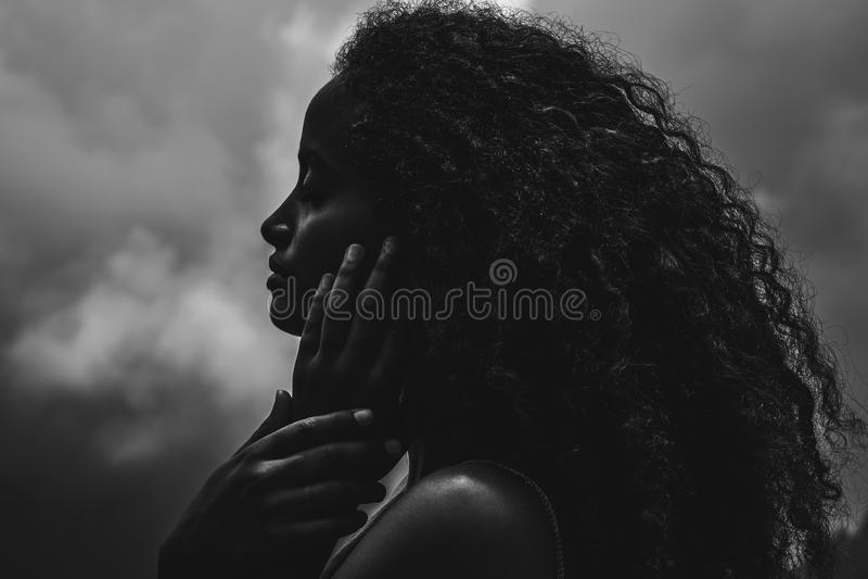 Portrait d'une belle femme ethnique d'afro-américain avec le nuage photographie stock libre de droits
