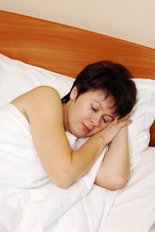 Portrait d'une belle femme heureuse dormant dans un lit photographie stock libre de droits
