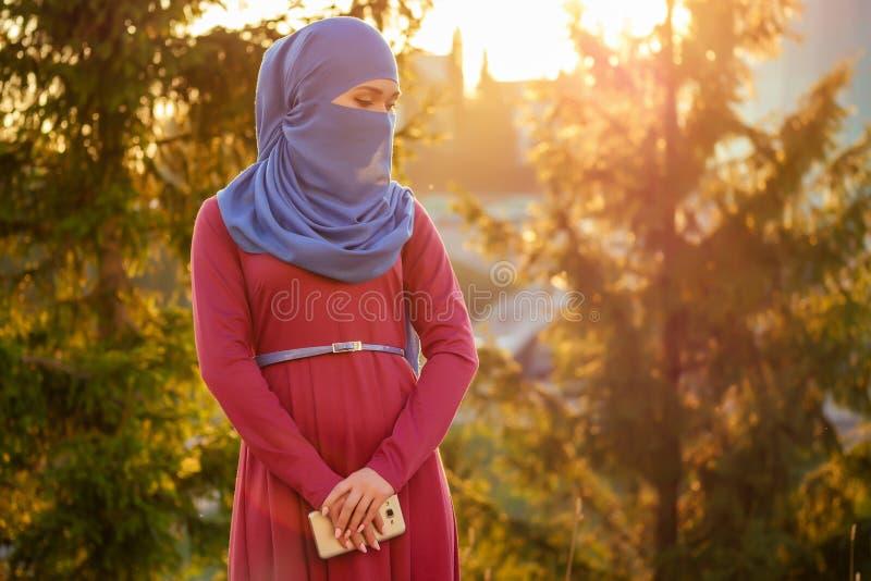 Portrait d'une belle femme musulmane aux yeux verts portant une écharpe bleue fermée recouverte d'une forêt de fond du Voile image stock