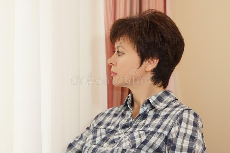 Portrait d'une belle femme regardant à une fenêtre photos stock