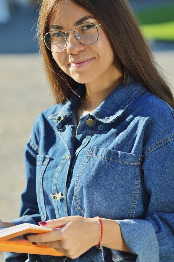 Portrait d'une belle fille asiatique en verres qui lit photos libres de droits