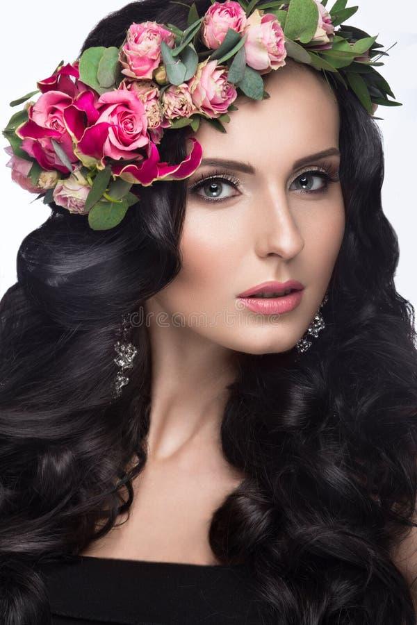 Portrait d'une belle fille avec un maquillage doux et un bon nombre de fleurs dans ses cheveux Image de ressort Visage de beauté photos stock