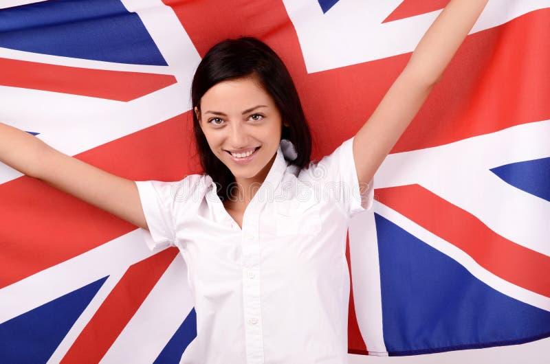 Portrait d'une belle fille britannique souriant supportant le drapeau BRITANNIQUE. images libres de droits