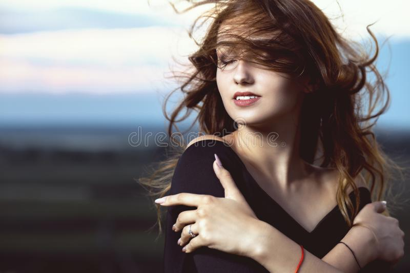 Portrait d'une belle fille contre le ciel nuageux de soirée, une jeune femme sur la nature images libres de droits