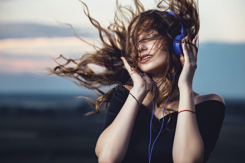 Portrait d'une belle fille dans des écouteurs avec des cheveux de vol du vent, jeune femme écoutant la musique sur la nature dans photo libre de droits