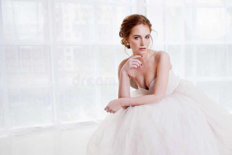 Portrait d'une belle fille dans une robe de mariage Jeune mariée dans la robe luxueuse se reposant sur une chaise photos stock