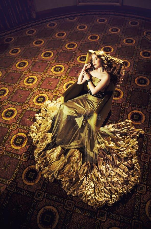 Portrait d'une belle fille dans une robe d'or dans le bel intérieur photos libres de droits