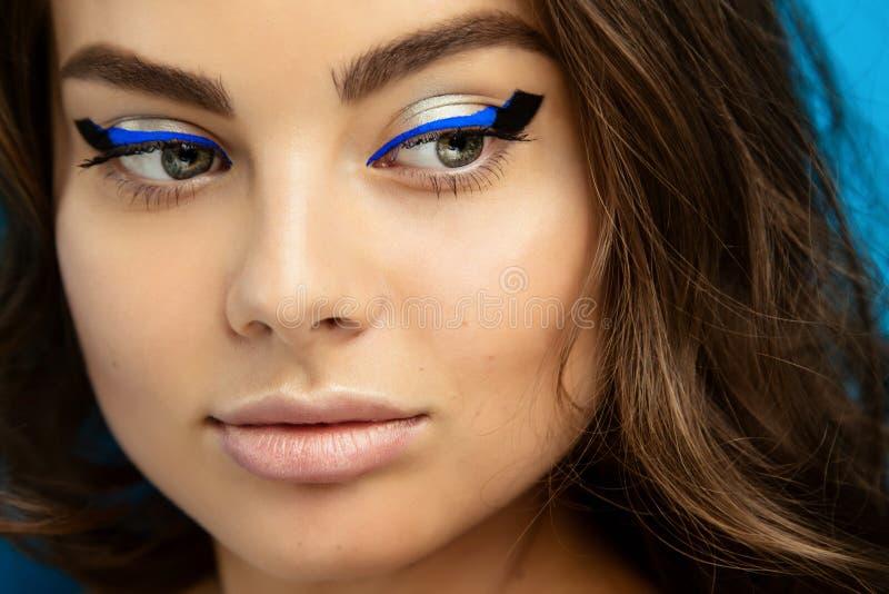 Portrait d'une belle fille de brune avec le maquillage de mode avec l'eye-liner noir et bleu photographie stock libre de droits
