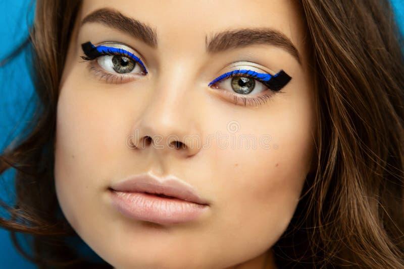 Portrait d'une belle fille de brune avec le maquillage de mode avec l'eye-liner noir et bleu image libre de droits