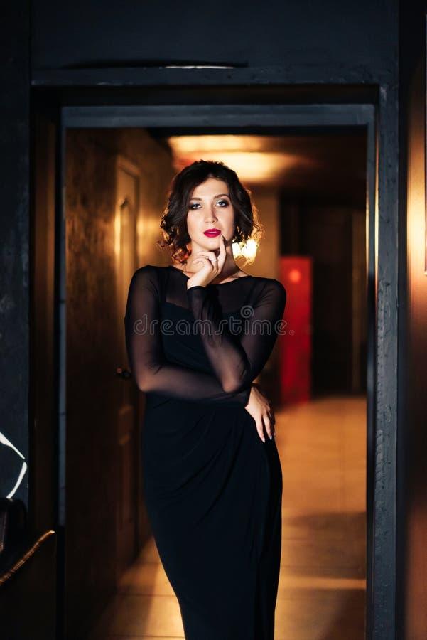 Portrait d'une belle fille de brune dans une robe noire dans une chambre noire 1 photo libre de droits