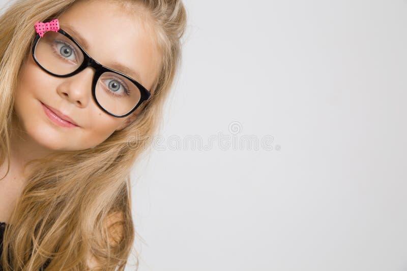 Portrait d'une belle fille de petite fille en longs cheveux blonds et verres noirs avec l'arc rose images libres de droits