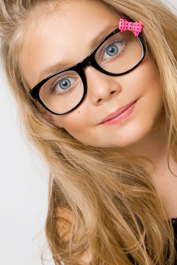 Portrait d'une belle fille de petite fille en longs cheveux blonds et verres noirs avec l'arc rose image stock