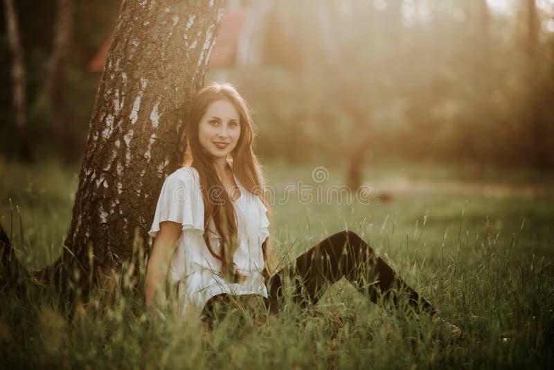 Portrait d'une belle fille en parc à la fille sunsetPretty avec l'extérieur de chandail dans le sourire de chute image libre de droits