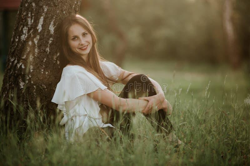 Portrait d'une belle fille en parc à la fille sunsetPretty avec l'extérieur de chandail dans le sourire de chute images libres de droits
