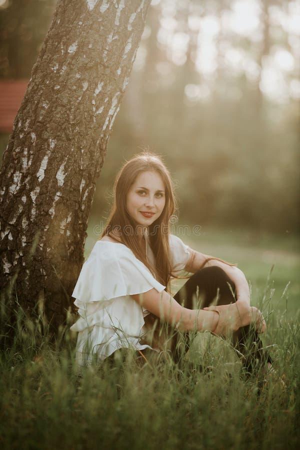 Portrait d'une belle fille en parc à la fille sunsetPretty avec l'extérieur de chandail dans le sourire de chute photos libres de droits