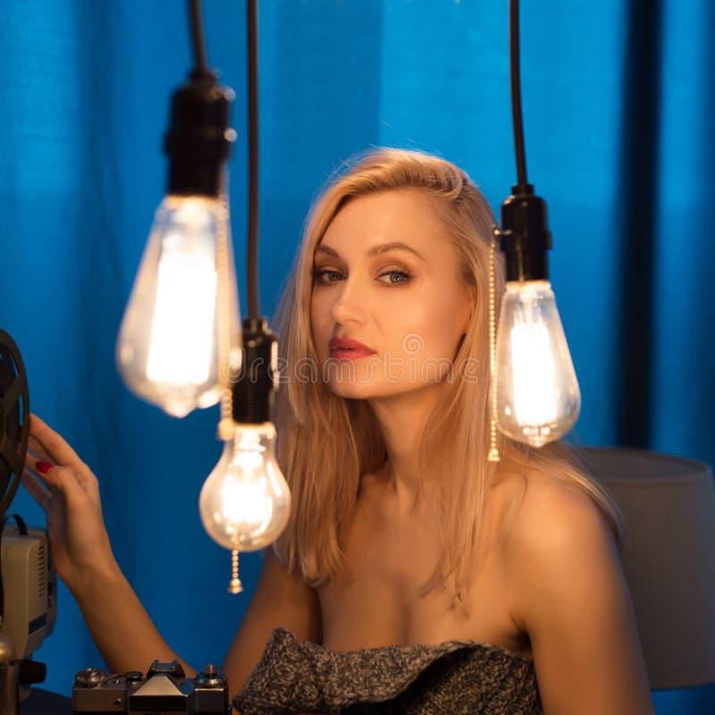 Portrait d'une belle fille européenne Une femme se tient près d'un mur entouré par les ampoules du ` s d'Edison images stock