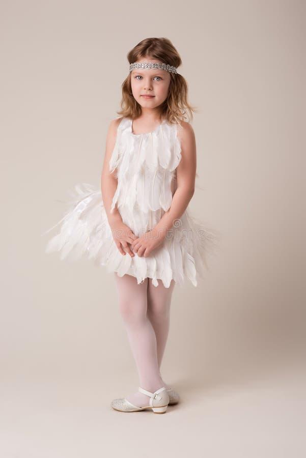 Portrait d'une belle fille gaie dans une robe des plumes blanches image stock