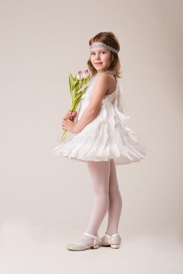 Portrait d'une belle fille gaie dans une robe des plumes blanches, avec des fleurs dans leurs mains images stock