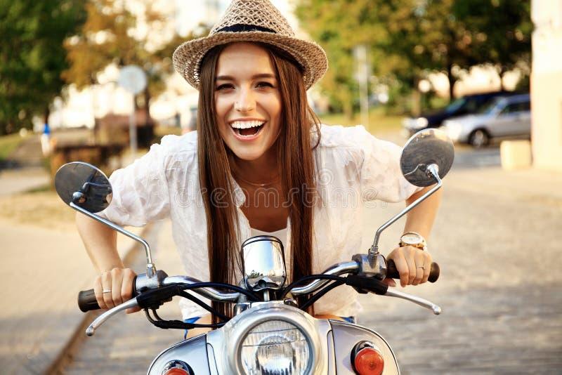 Portrait d'une belle fille s'asseyant sur le rétro scooter argenté, souriant et regardant l'appareil-photo photo libre de droits