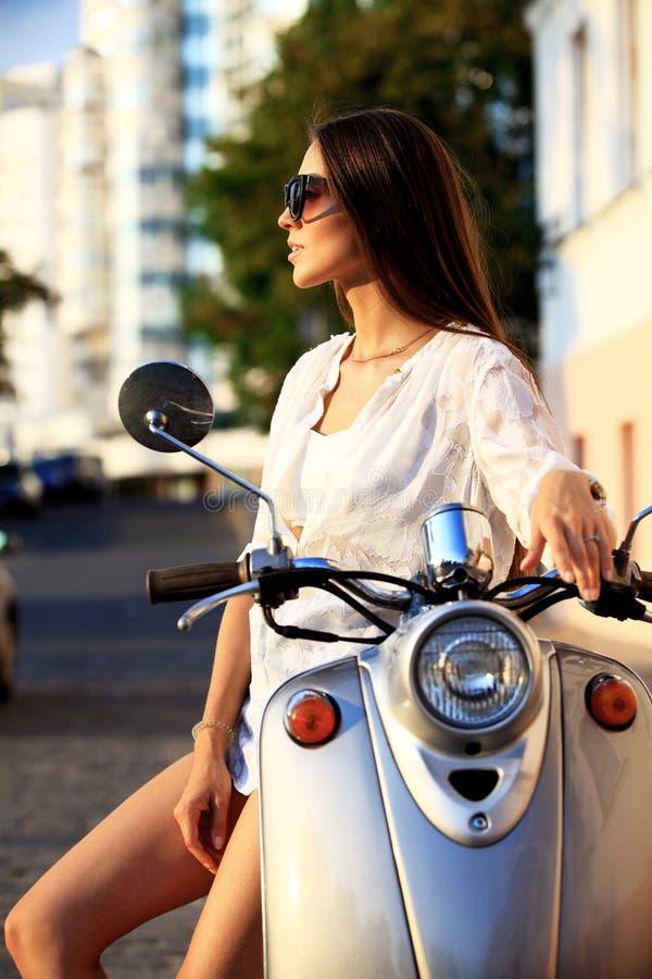 Portrait d'une belle fille s'asseyant sur le rétro scooter argenté, souriant et regardant l'appareil-photo photos libres de droits