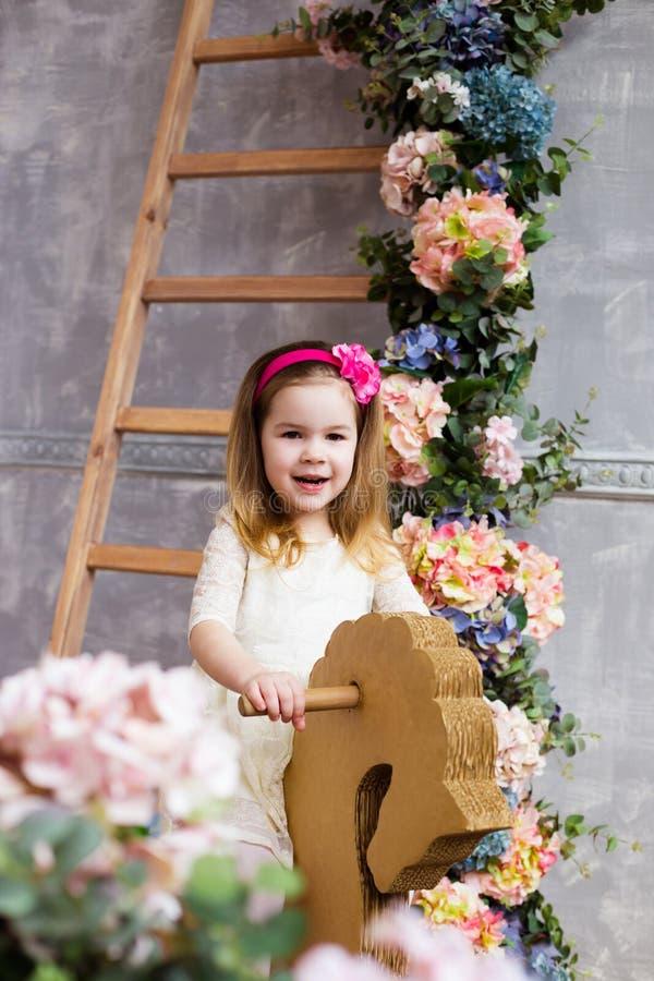 Portrait d'une belle fille sur un cheval de basculage en bois dans le RO photos stock