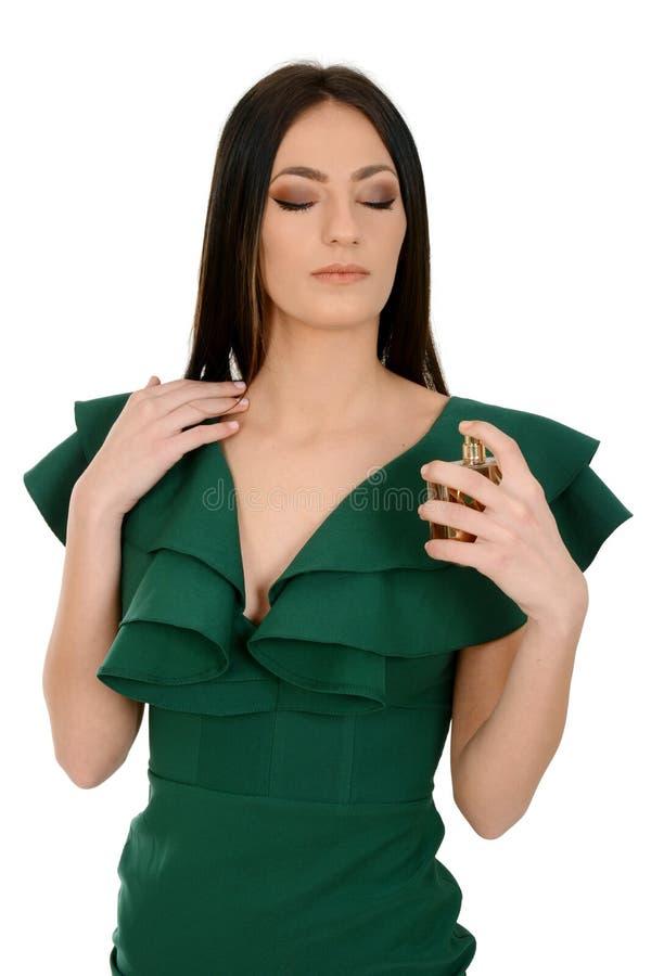 Portrait d'une belle jeune femelle dans la robe verte appliquant un parfum photo libre de droits