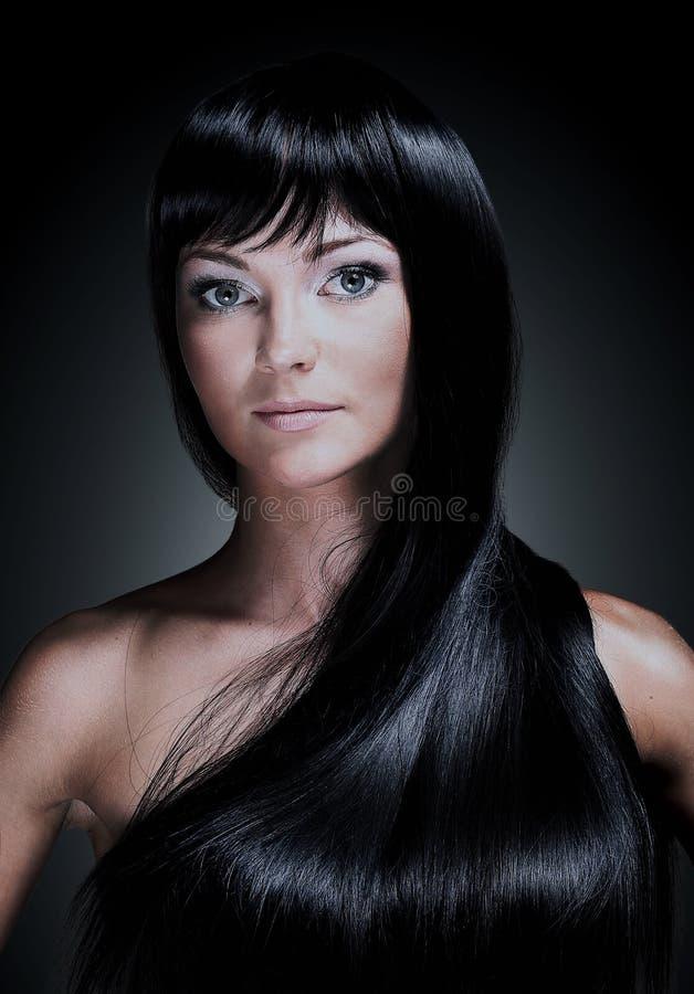 Portrait d'une belle jeune femme avec de longs cheveux brillants élégants D'isolement sur le fond noir image libre de droits