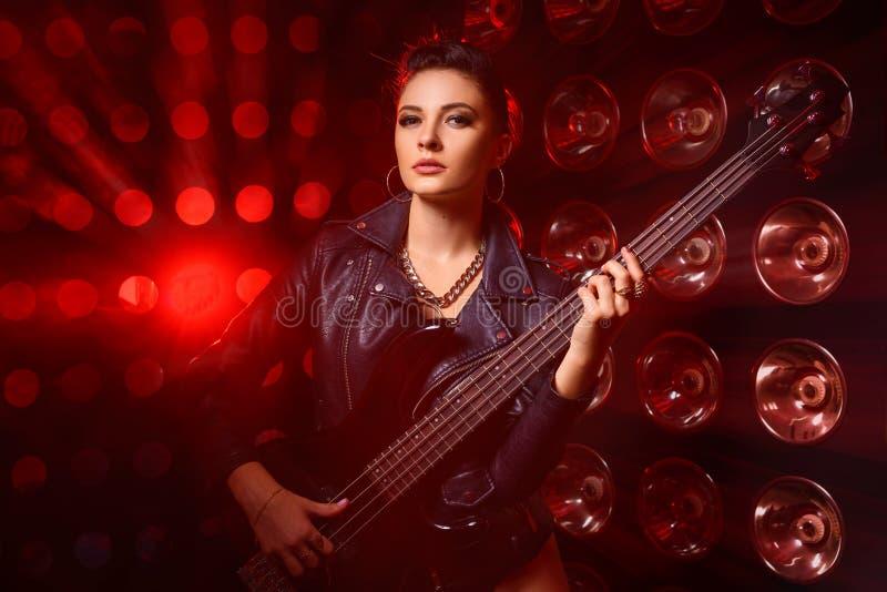Portrait d'une belle jeune femme avec une guitare électrique images libres de droits