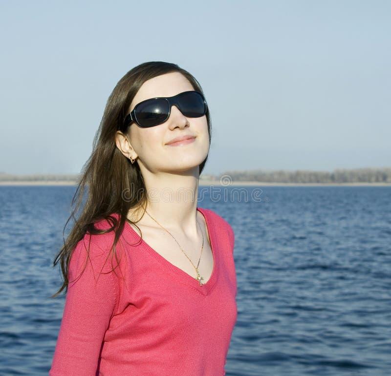 Portrait d'une belle jeune femme dans des lunettes de soleil au-dessus de b photographie stock libre de droits