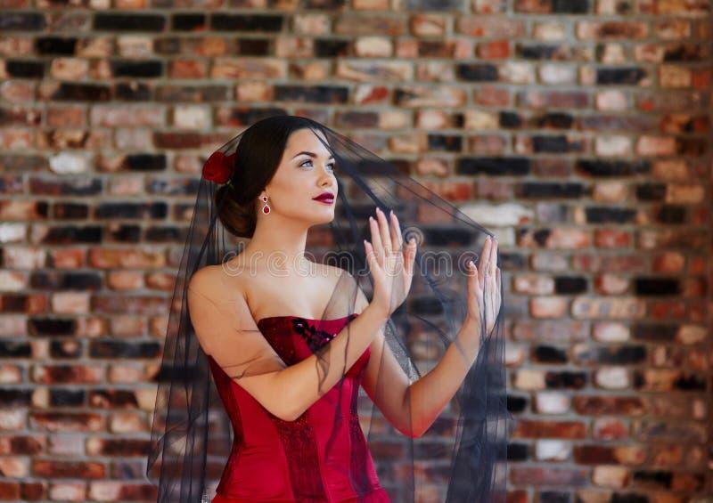 Portrait d'une belle jeune femme dans une robe rouge sous un noir photographie stock