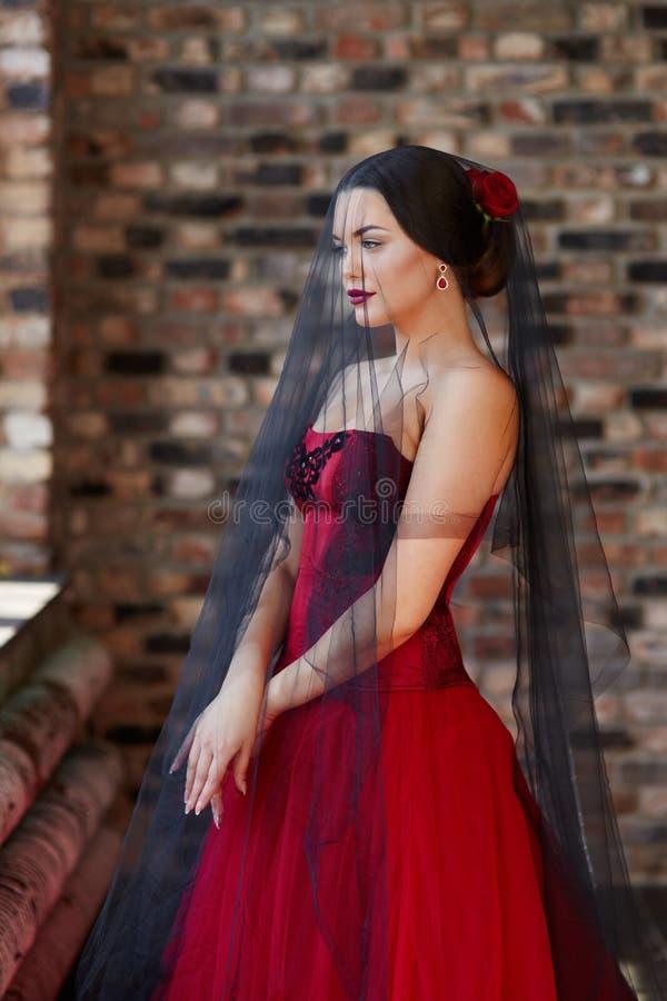 Portrait d'une belle jeune femme dans une robe rouge sous un voile noir images libres de droits