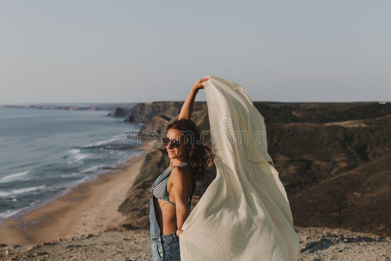 Portrait d'une belle jeune femme heureuse jouant avec un mouchoir et le vent sur le dessus d'une colline Jeunes adultes lifestyle photos libres de droits