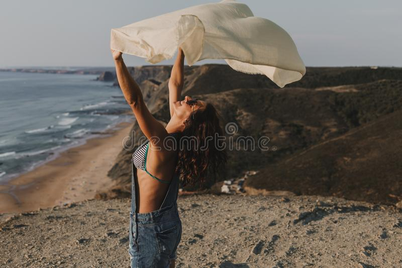 Portrait d'une belle jeune femme heureuse jouant avec un mouchoir et le vent sur le dessus d'une colline Jeunes adultes lifestyle photo stock