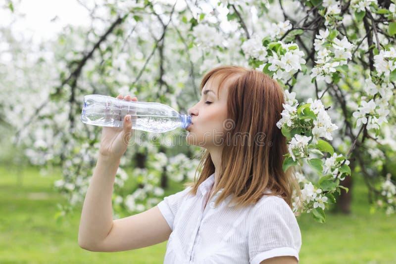 Portrait d'une belle jeune femme qui boit l'eau dans l'AMO de parc photos libres de droits