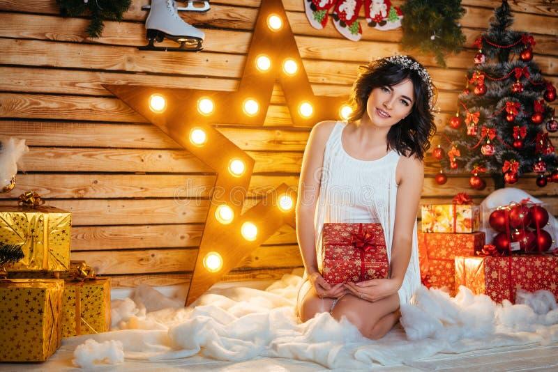 Portrait d'une belle jeune femme qui tient un cadeau pour la nouvelle année et le Noël photos stock