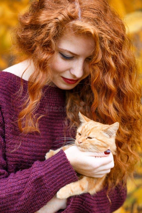 Portrait d'une belle jeune femme rousse tenant un chat images libres de droits