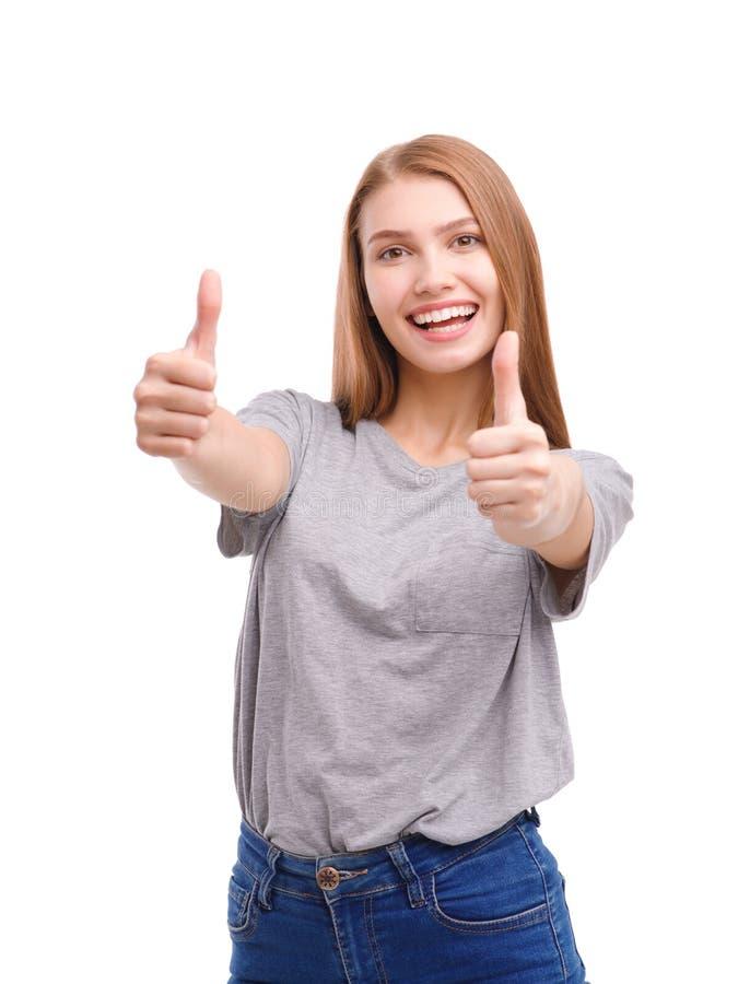 Portrait d'une belle jeune fille, augmenté ses pouces, souriant, d'isolement sur le fond blanc image libre de droits