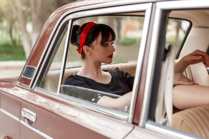 Portrait d'une belle jeune fille caucasienne dans une robe noire de cru, posant dans la cabine d'une voiture de cru images libres de droits