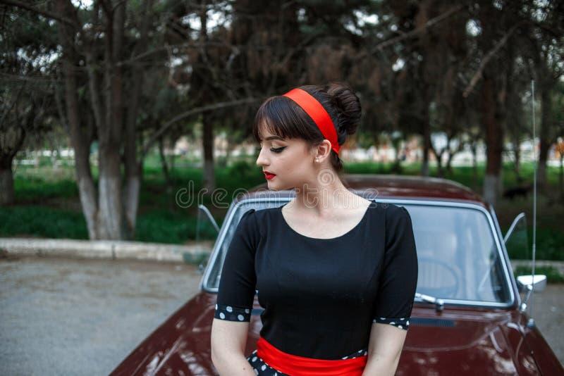 Portrait d'une belle jeune fille caucasienne dans une robe noire de cru, posant près d'une voiture de cru photographie stock libre de droits