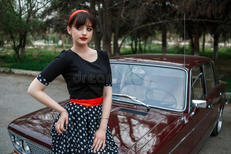 Portrait d'une belle jeune fille caucasienne dans une robe noire de cru, posant près d'une voiture de cru photo libre de droits