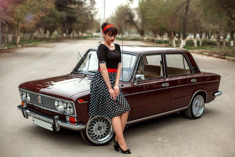 Portrait d'une belle jeune fille caucasienne dans une robe noire de cru, posant près d'une voiture de cru image stock