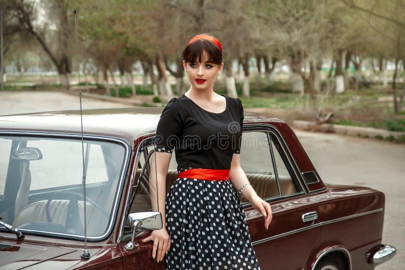 Portrait d'une belle jeune fille caucasienne dans une robe noire de cru, posant près d'une voiture de cru images libres de droits