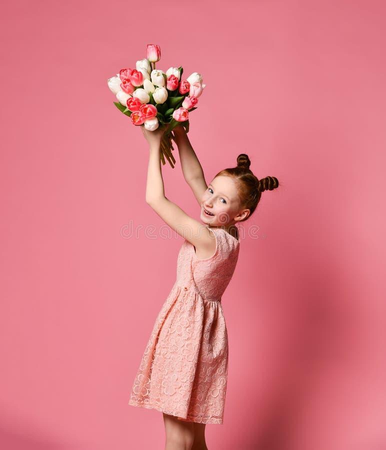 Portrait d'une belle jeune fille dans la robe tenant le grand bouquet des iris et des tulipes d'isolement au-dessus du fond rose photo libre de droits