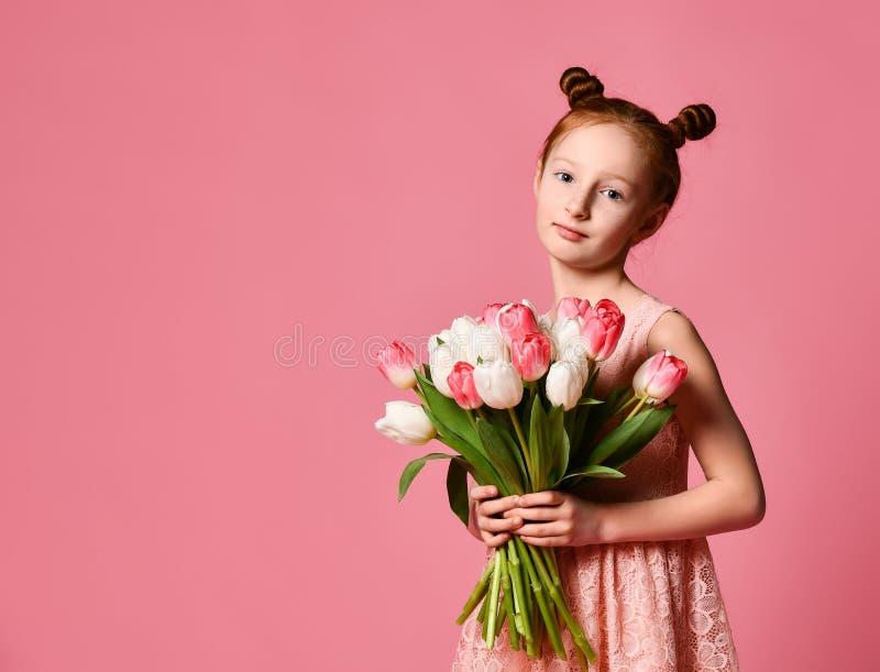 Portrait d'une belle jeune fille dans la robe tenant le grand bouquet des iris et des tulipes d'isolement au-dessus du fond rose photo stock