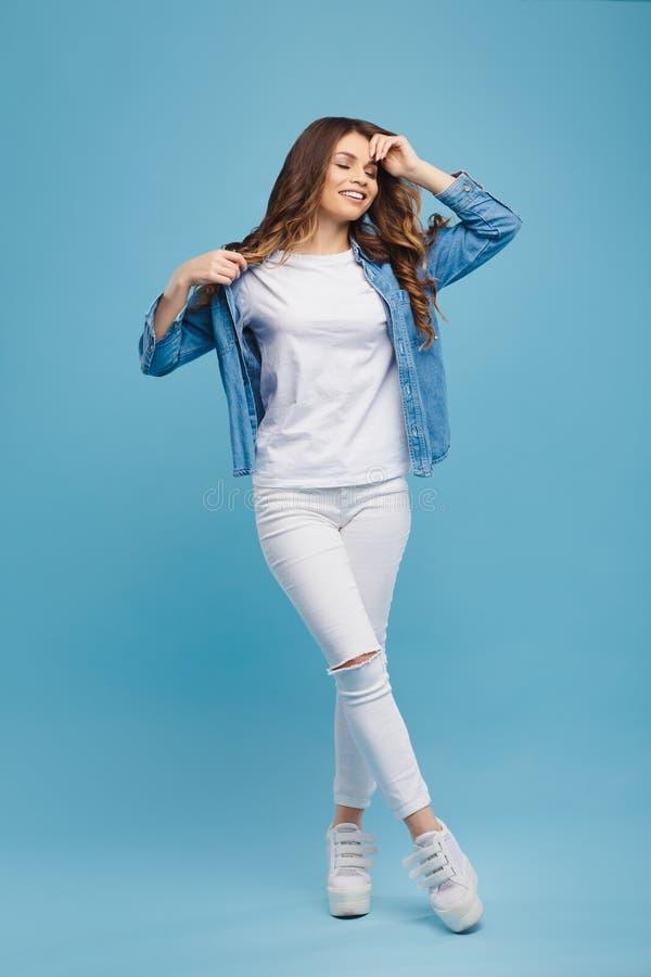 Portrait d'une belle jeune fille posant sur un fond bleu photos stock