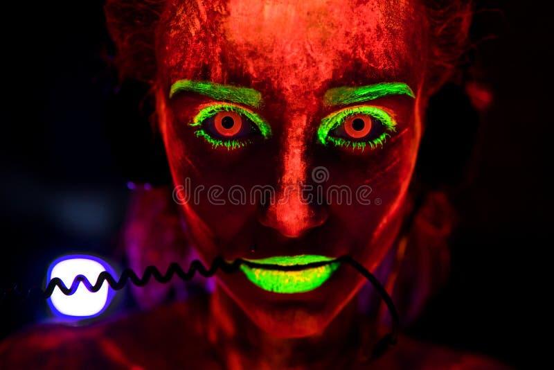 Portrait d'une belle jeune fille sexy dans des écouteurs avec la peinture ultra-violette sur son corps Jolie femme avec rougeoyer image libre de droits
